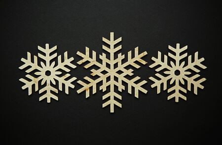 Beautiful hand made wooden snow flakes in flat lay on black background.Winter holiday home decor made with eco friendly materials.Decorate house for Christmas & Happy New Year with handmade toys