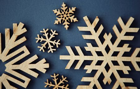 Flat lay background.Handmade wooden snowflakes for winter holidays.Christmas Eve & Happy New Year decorations made from rustic wood material on blue paper background shot from above in flat layout