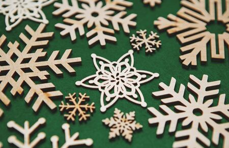 Handmade wooden snowflakes in flat lay on green background for winter holidays decoration.Hand made crafts for Happy New Year and Christmas holiday home decor.Rustic style snow flake figures in close