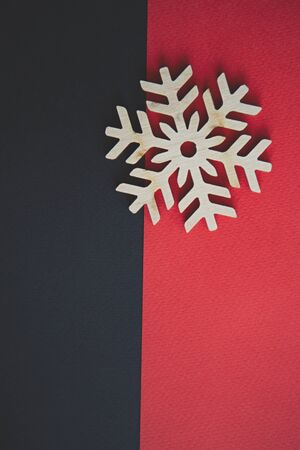 Handmade wooden snowflakes on red and black background in flat lay style.Winter holiday backdrop with eco friendly toy snow flake made from natural wood material