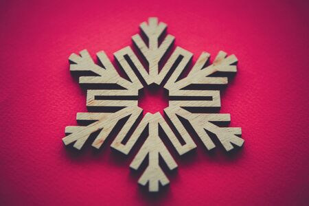Wooden snow flake on red background for Christmas and New Year celebration.Handmade crafts for winter holidays home decor.Hand made decorative snowflake made from eco friendly rustic wood material