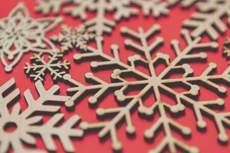 Handmade wooden snowflakes for Christmas background.Red New Year celebration backdrop with hand made crafts made from eco friendly wood material