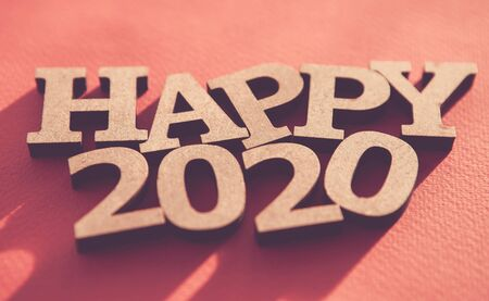Happy 2020 background.Red wallpaper with wooden rustic style letters shot on paper backdrop,edited with fading film filter and low contrast.Winter holiday poster