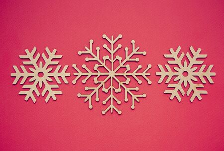 Winter holidays flat lay background.Red backdrop with handmade wooden snowflakes for Christmas and New Year celebration party decor.Vibrant poster with hand made crafts for decoration