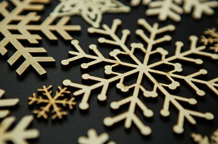 Wooden snow flakes on black background.Rustic style home decor for Christmas and New Year holidays celebration.Vintage style snowflakes made from natural,eco friendly wood material