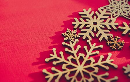 Red Christmas background with handmade wooden snowflakes.Hand crafted and eco friendly home decor for winter holidays.New Year decor in close up for wallpaper 写真素材