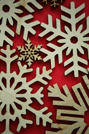 Hand crafted wooden snow flakes on red background.Eco friendly home decor for winter holidays.Decorate house with natural ecological materials for Christmas Eve and Happy New Year celebration party