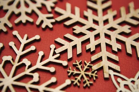 Red Christmas background with hand made eco friendly wooden snowflakes in flat layout.Handmade wood crafts for winter holidays home decor.New Year decoration in closeup,edited with vintage film filter 写真素材
