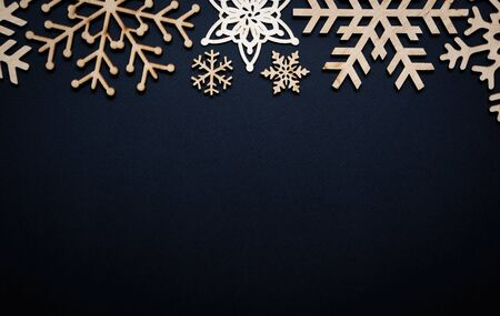 Winter holiday background.Hand made wooden rustic snowflakes on black paper backdrop for Christmas Eve and Happy New Year poster.Empty space on wallpaper for text