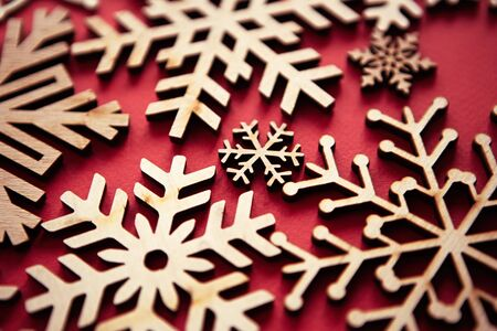Hand made wooden snowflakes on red Christmas background.Handmade rustic crafts for winter holidays wallpaper. 写真素材