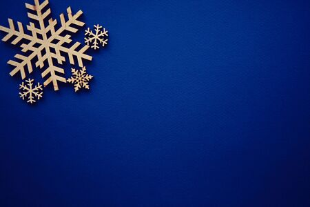 Blue winter holiday background with handmade wooden snowflake.Paper backdrop with hand crafted snow flake figure made from rustic wood material.Christmas wallpaper with empty space for text