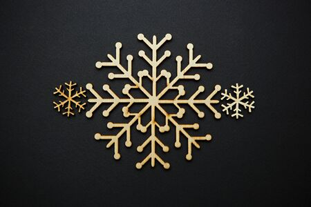 Handmade wooden rustic snow flakes on black backgound.Winter holiday decorations in flat lat style.Beautiful hand made crafts for Christmas Eve and Happy New Year decoration