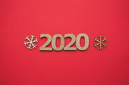 Red Christmas background with 2020 figures and wooden snow flakes shot from above in flat lay style.Handmade crafts for winter holiday celebration.Hand made decor for wallpaper