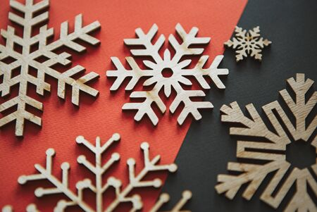 Wooden rustic snowflakes in flat lay on red & black Christmas background.Handmade snow flake figures for New Year home decor.Eco friendly natural wood material for decorations