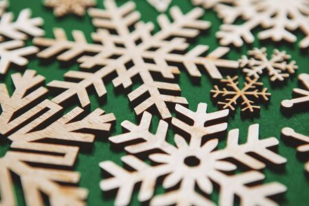 Handmade snowflakes on green Christmas background.natural eco friendly toys made from rustic wood material,shot in close up