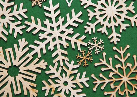Wooden snowflakes in flat lay on green background.Christmas toys made from rustic wood material.New Year decorations in flat layout for wallpaper design.Handmade crafts for winter holidays home decor