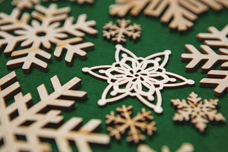 Wooden rustic snowflakes on green Christmas background.Handmade rustic wood decoration and toys for winter holidays shot in close up.New Year toy made from natural,eco friendlyt rustic material