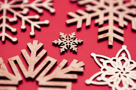 Beautiful handmade wooden snowflakes for winter holidays.Red background with hand made crafts made from ecological natural wood material.Eco friendly home decor for Christmas and New Year celebration 写真素材