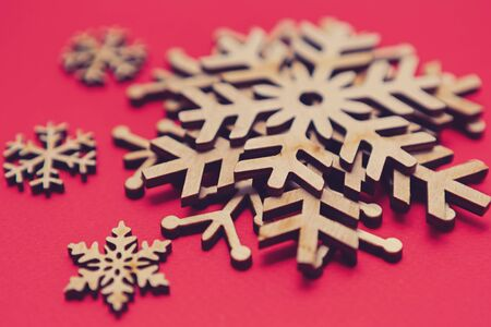 Christmas toys on red background.Handmade snowflakes made from wood.Eco friendly wooden rustic snow flakes for home decor.Hand made crafts for winter holidays 写真素材