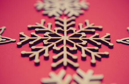 Handmade wooden snowflakes on red background in flat layour for winter holiday decor.Christmas backdrop with hand made crafts shot in close up