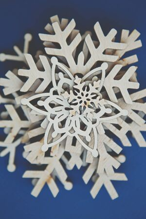 Beautiful handmade wooden snowflakes in flat lay on blue background.Hand made crafts for home decor on winter holidays,shot from above