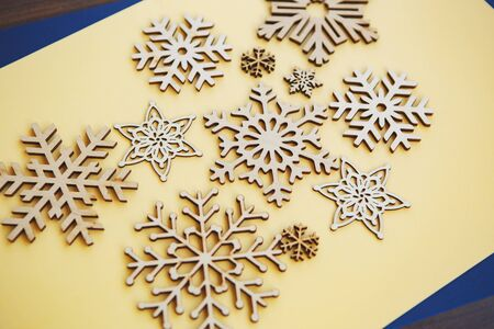 Winter holiday background with handmade wooden snowflakes.Hand made crafts for Christmas and New Year home decor shot from above on yellow background.Beautiful ecological decorative elements for house 写真素材