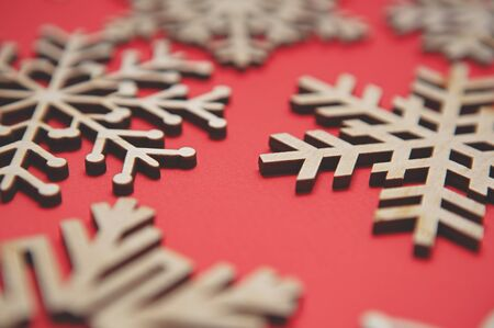 Rustic wooden snowflakes for Christmas decorations.Hand made snow flake on red background.Beautiful handmade crafts made from eco friendly natural wood material.