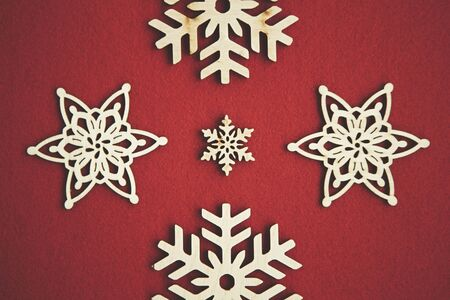 Flat lay handmade wooden snowflakes for Christmas background.Snow flake figures made from natural eco friendly rustic wood material,shot in flat layout from above on red backdrop.Winter holidays decor 写真素材