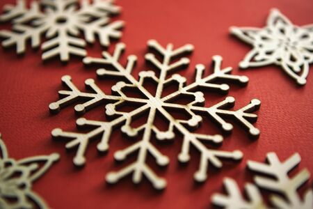 Handmade Christmas snowflake toy on red background.Hand made wooden crafts for home decoration in winter holiday season.Rustic snowflakes for New Year decorations,edited with vintage style film filter 写真素材