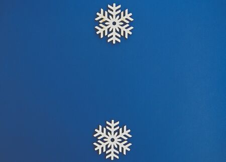 Blue winter holiday background.Flat lay wooden snowflakes on empty backdrop for Merry Christmas & Happy New Year wallpaper design.Place text on empty space for holidays poster