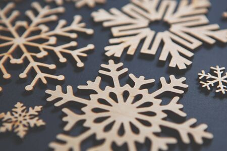 Beautiful handmade wooden Christmas snowflakes on blue background.Hand made crafts made from eco friendly natural wood material.Ecological home decor for winter holidays in close up