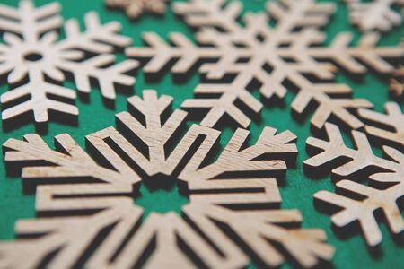 Handmade wooden Christmas snowflakes on green background.Beautiful snow flake figures made from natural eco friendly wood material for winter holidays home decor.Ecological decorations for New Year
