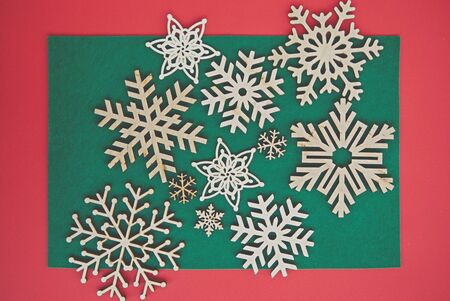Handmade wooden snowflakes in flat lay on Christmas themed background.Red & green backdrop with hand made crafts for winter holidays.New Year home decor made from ecological  wood material
