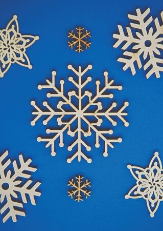 Handmade wooden snowflakes in flay lay on blue Christmas background.Decorative hand made crafts for winter holidays.Ecological wood snow flakes for New Year home decor,shot in vertical from above 写真素材