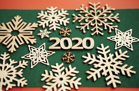 2020 winter holidays background.Handmade wooden snowflakes on green backdrop.Merry Christmas and Happy New Year wallpaper with hand made crafts precisely cut from ecological natural wood material