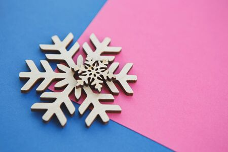 Rustic Christmas snowflakes made from wood.Beautiful handmade wooden toys for home decor.Winter holidays decorations shot in close up on pink and blue background