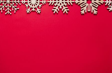 Red Christmas background.Flat lay backdrop with handmade wooden snowflakes on paper backdrop.Empty space for text on New Year poster template.Winter holidays wallpaper with minimalistic design