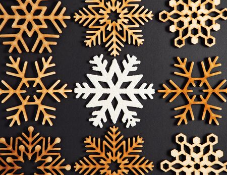 Flat lay black Christmas background.Wooden decorative snowflakes shot directly from above.New Year celebration party poster template with rustic toys made from wood.Dark winter holidays wallpaper 写真素材