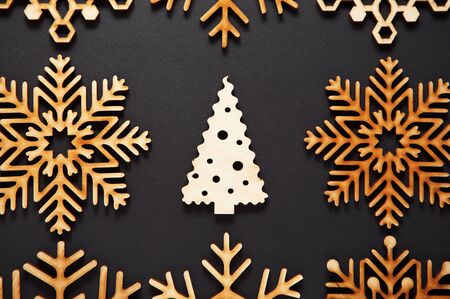 Black flat lay background for Christmas party poster.Decorative wooden fir tree and rustic snowflakes shot from above on paper backdrop for winter holiday postcard design.Natural wood material