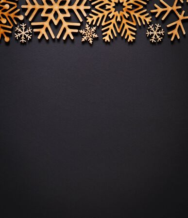 Black flat lay background with Christmas decorations.Hand crafted snowflakes on dark backdrop.Rustic handmade wallpaper with empty space for text.New Year celebration party poster template