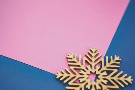 Pink and blue paper background with hand made wooden decorative snow flake.Hand crafted winter holiday decor element in close up