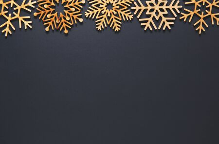 Black flat lay background.Christmas toys on wallpaper.Handmade wooden decorations for New Year party poster design.Empty space on postcard template for winter holiday celebration party