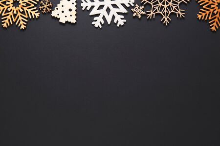 Flat lay Christmas background.Handmade New Year decorations on black poster with empty space for text.Winter holiday postcard template in flat layout style.Rustic wooden snowflakes on wallpaper