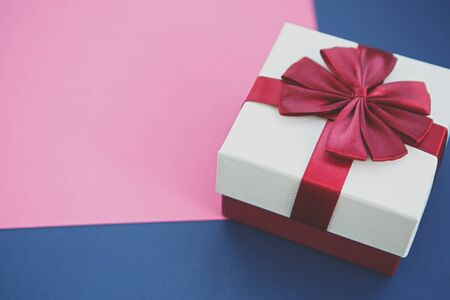 White Christmas present box with red ribbon on pink & blue paper backgrounds.Decorative New Year gift box in close up