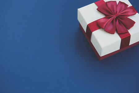 Gift box with red ribbon on blue background.Christmas & New Year present package in white and red colors decorated with bow.Beautiful minimalistic wallpaper with empty space for text