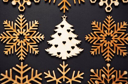 Flat lay wooden Christmas tree toy on black background.Rustic handmade decorations shot from above.Beautiful hand crafted decor elements for winter holidays