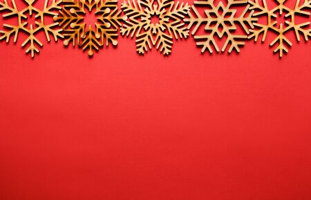 Red Christmas background.Flat lay wooden snowflakes shot directly from above.New Year party poster template with copy space for text.Rustic toys made from natural wood materials 写真素材