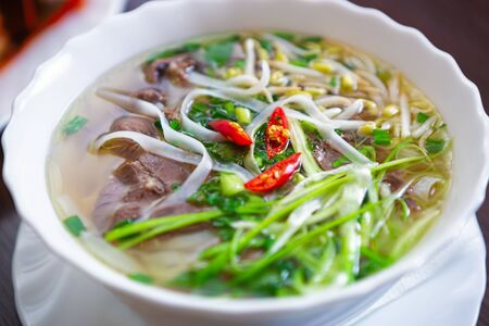 Asian food.Vietnamese pho bo soup with beef meat,rice noodles in broth and spices served in white bowl.Traditional Vietnam cuisine in close up.Delicious natural ingredients from Asia Stock Photo