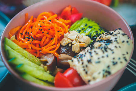 Delicious poke bowl dish served for lunch in Asian restaurant.Traditional Hawaiian cuisine dish with fresh avocado,cucumbers,hummus,korean carrots & mushrooms served in ceramic plate at vegan cafe