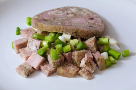 brawn: Pork brawn sliced with spring onion on white isolated background.
